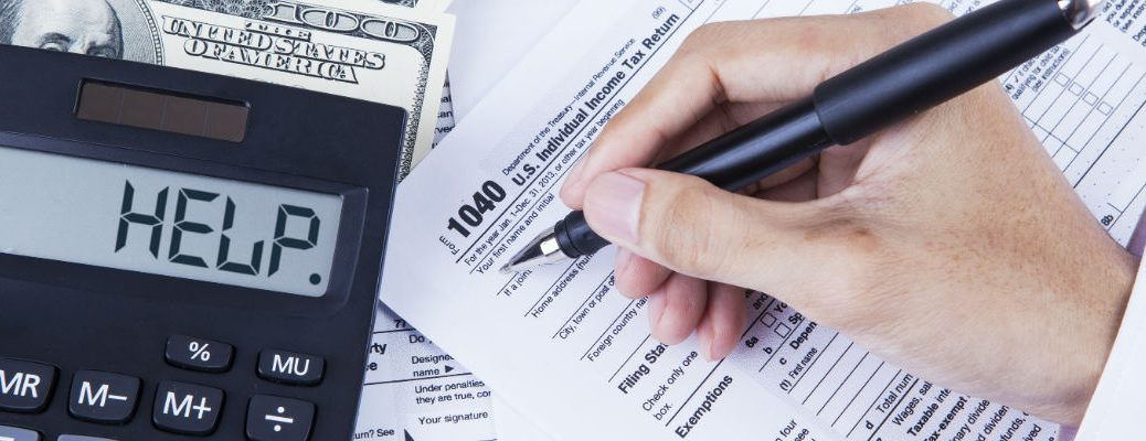 A stock photo of a person filling out their taxes.