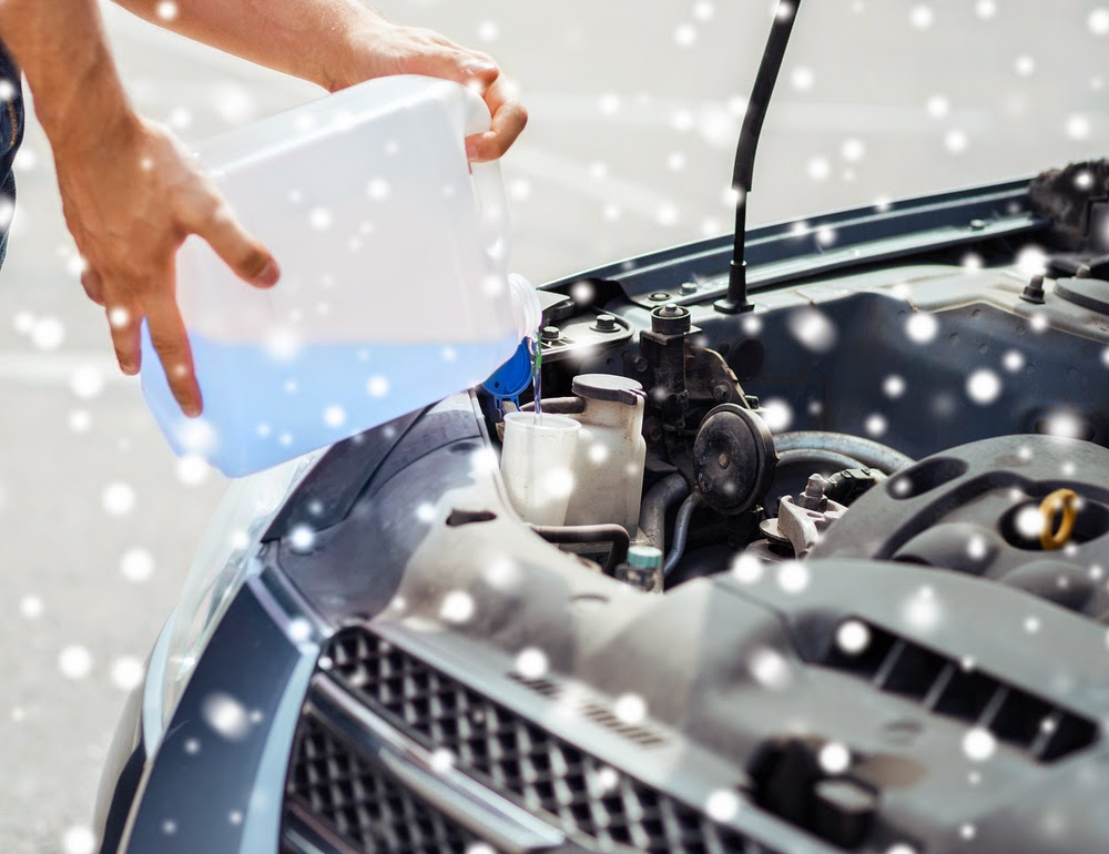 man adding windshield wiper fluid to car - how to winterize vehicle