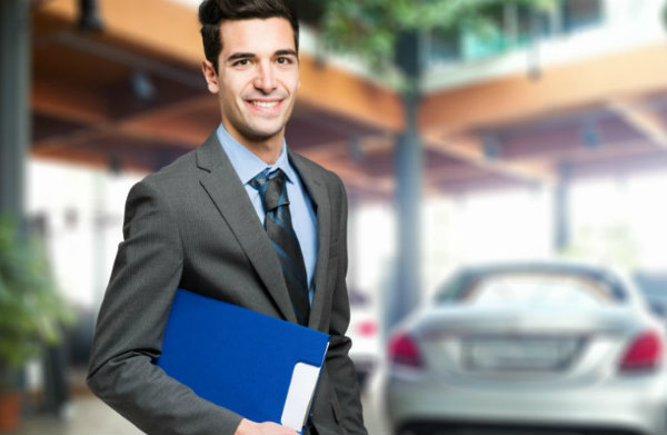 Man in suite holding blue folder with car in background