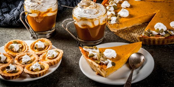 Pumpkin pie and tarts on table
