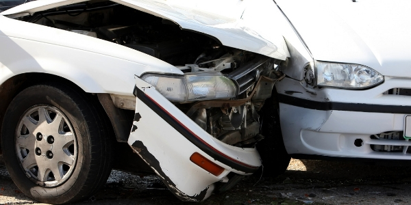 Closeup of two white cars in an accident
