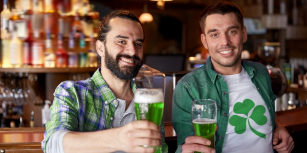 Two men holding green beers in a bar