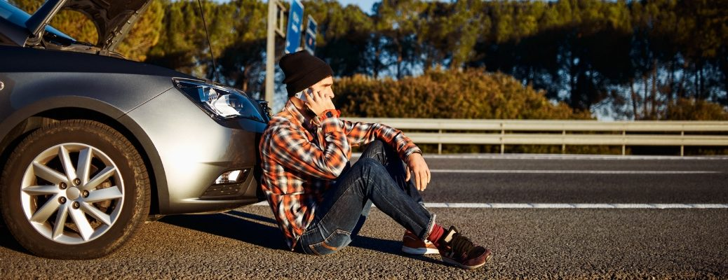 Man sitting on ground in front of vehicle calling for help