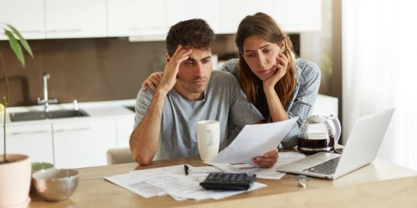 Stressed couple in front of computer looking at papers