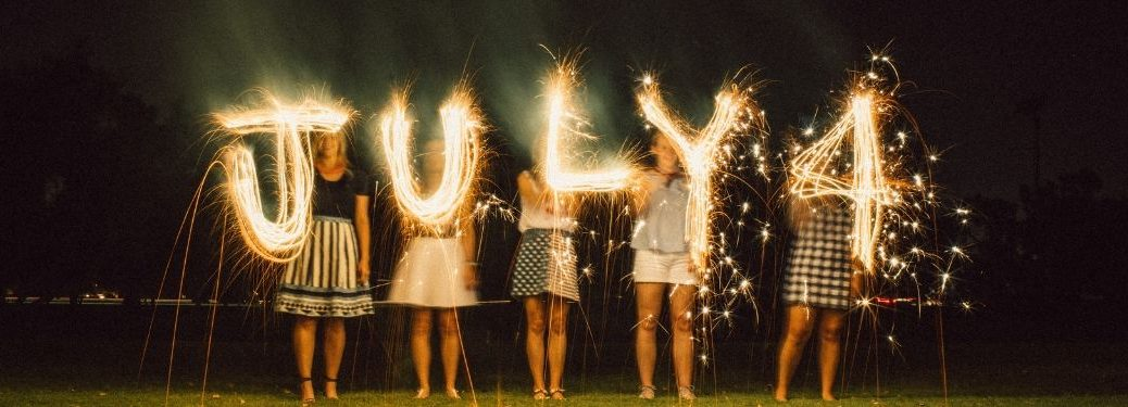 "girls spelling out ""JULY 4"" with sparklers"
