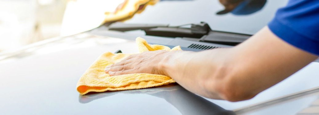 Person giving their car a wax with a yellow microfiber cloth