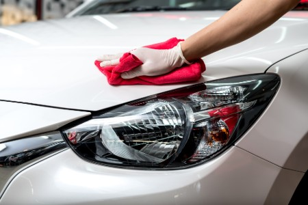 Close up of the driver headlight on a white car with a person giving the hood a wax with a red cloth