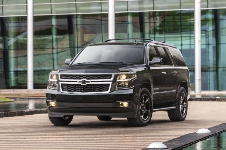Front driver angle of a black 2019 Chevrolet Suburban parked in front of a building