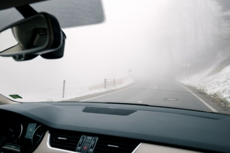 Front passenger seat view of heavy fog while driving on a road