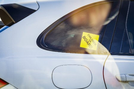 A yellow Children on Board sticker on the rear passenger window of a white vehicle