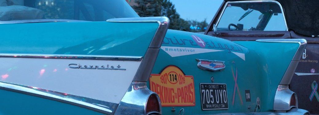 Rear driver angle of an antique Chevrolet vehicle with car stickers on the rear end