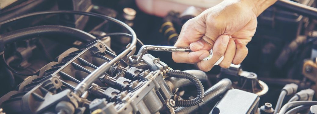 hand using a tool on an engine