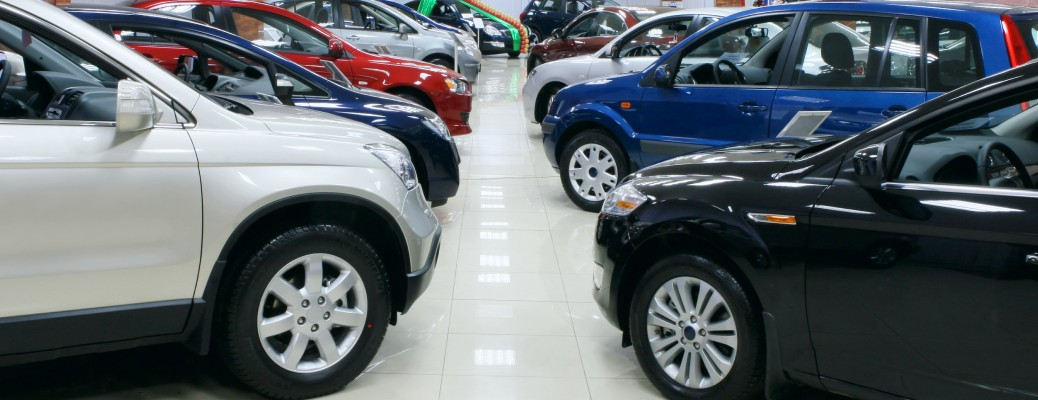 A variety of SUVs and cars lined up indoors at a dealership