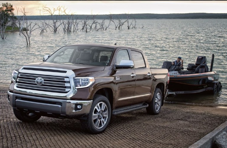 A 2021 Toyota Tundra towing a boat either in or out of a body of water while parked on a planked pier