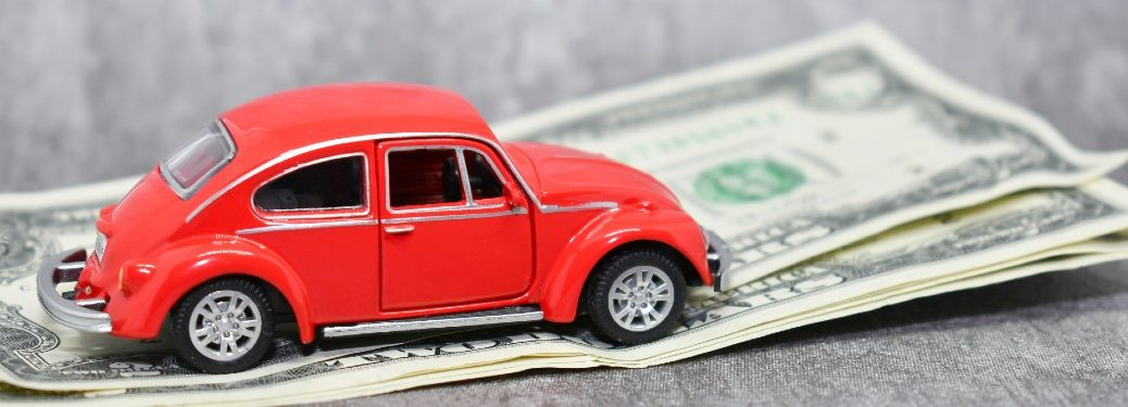 small toy red car on top of small stack of dollar bills