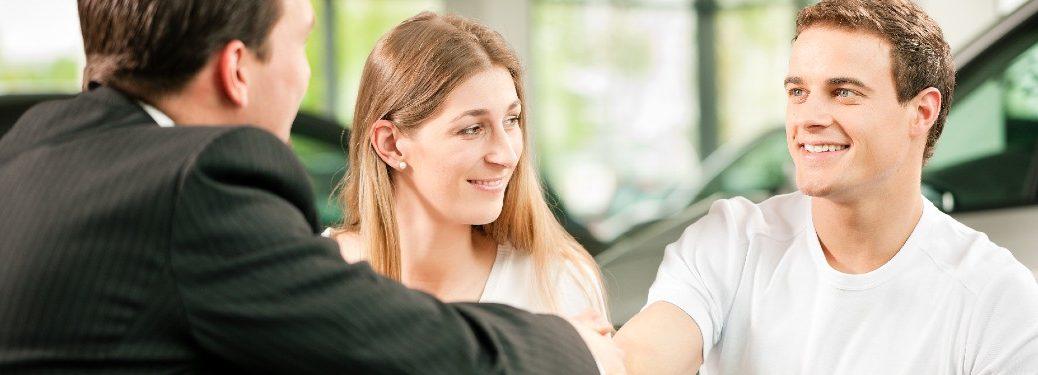 couple at dealership man shaking hand of salesman after purchase