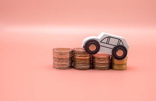 small white wooden toy car driving on stacks of coins on pink background