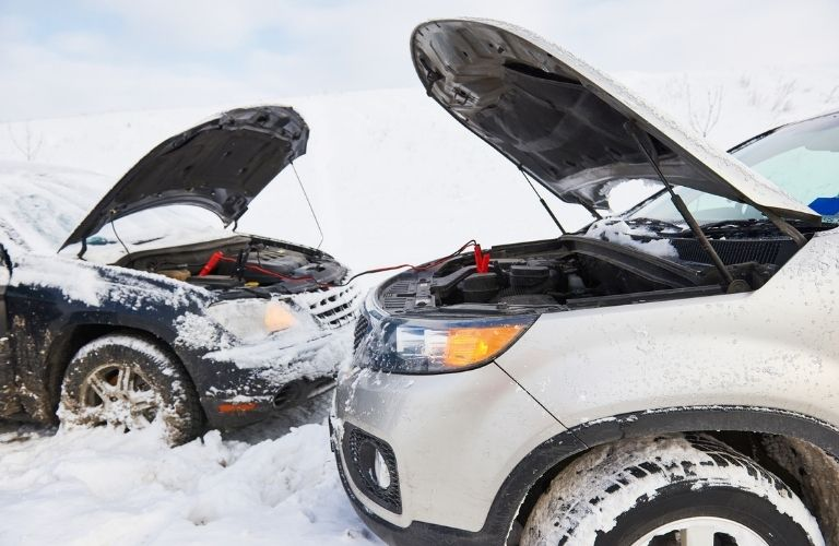 Jumper cables attached to two cars in winter season with heavy snow