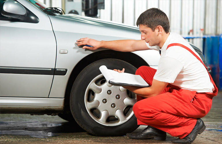 Technician Servicing a Car in Red Overalls
