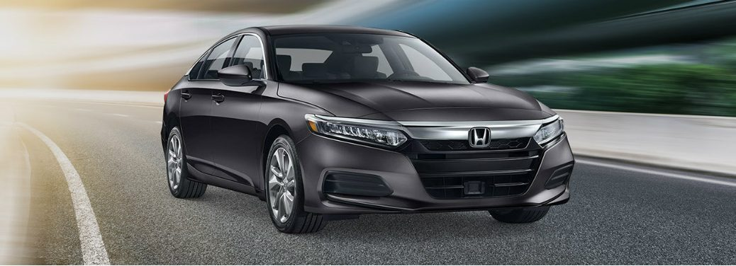 Dark grey 2019 Honda Accord drives down a stylized highway. Front angled exterior view.
