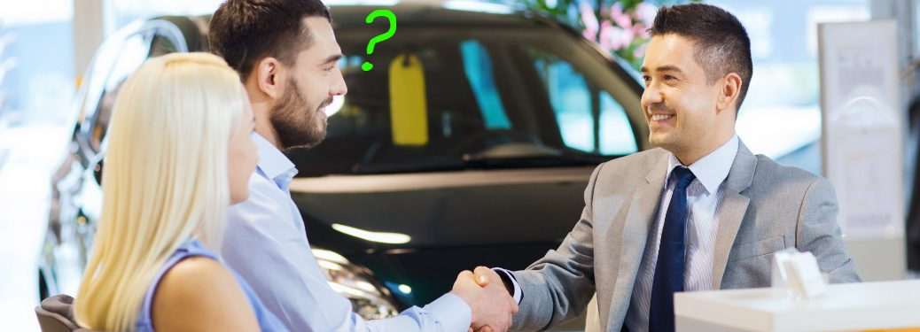 A man shakes the hand of a salesman and asks a question.