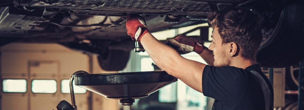 professional car mechanic changing oil of vehicle