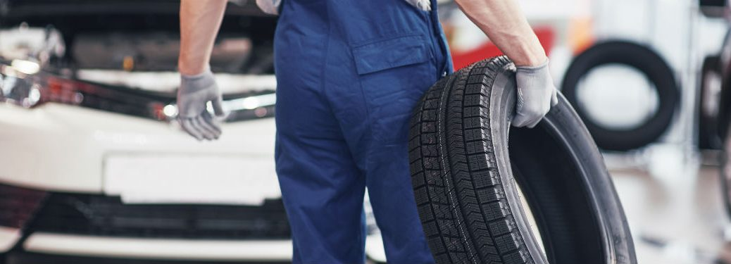 mechanic holding tire and walking toward car