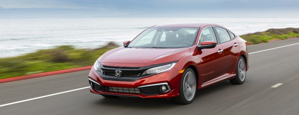 2020 Honda Civic Sedan Touring red driving past body of water