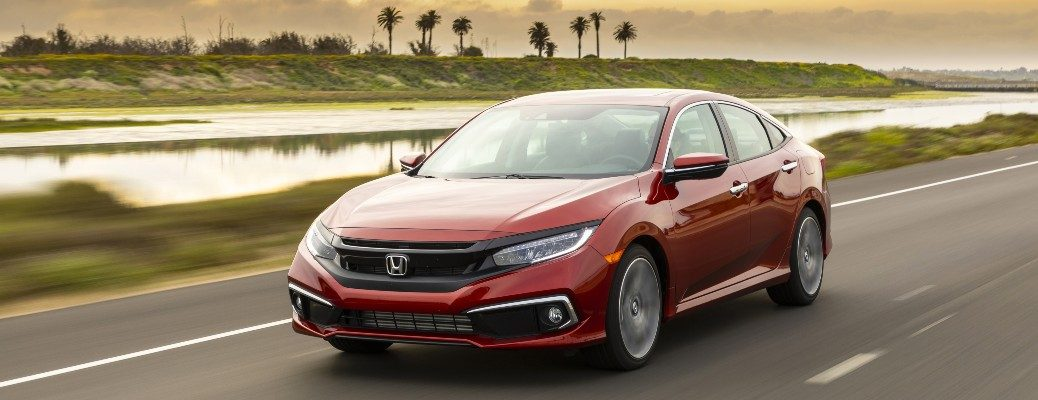 2020 Honda Civic Sedan Touring red driving past water with palm trees in background
