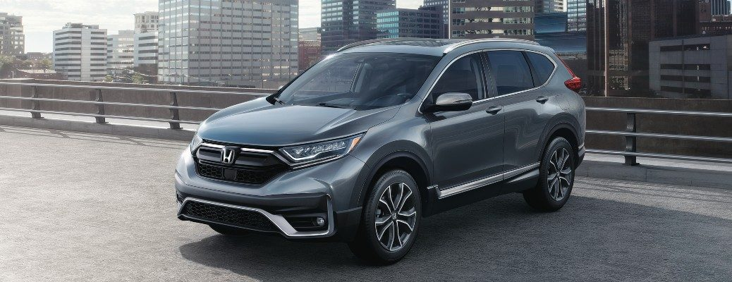 2020 Honda CR-V Touring gray parked on concrete by railing with skyline