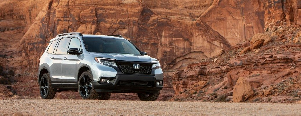 2020 Honda Passport silver parked on gravel in front of rock wall