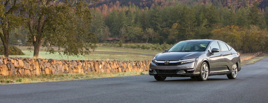 2020 Honda Clarity Plug-In Hybrid gray color driving on road past short stone fence