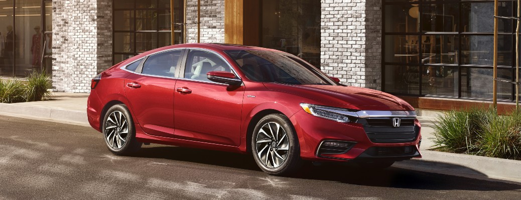 2021 Honda Insight red parked facing right in front of brick building with windows