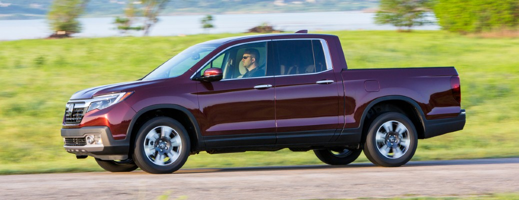 2020 Honda Ridgeline red driving to the left person driving 2018 model shown