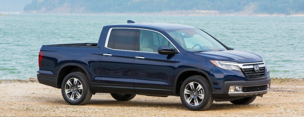2020 Honda Ridgeline blue parked on sand in front of water 2018 model shown