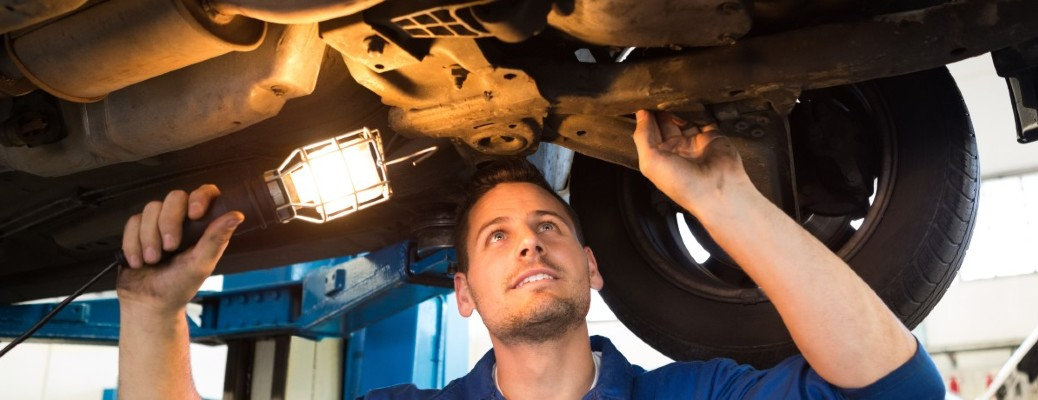 stock photo of mechanic looking under vehicle with work light