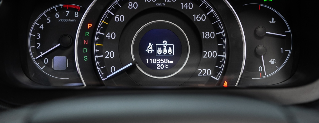 close up on odometer in vehicle with gauge cluster