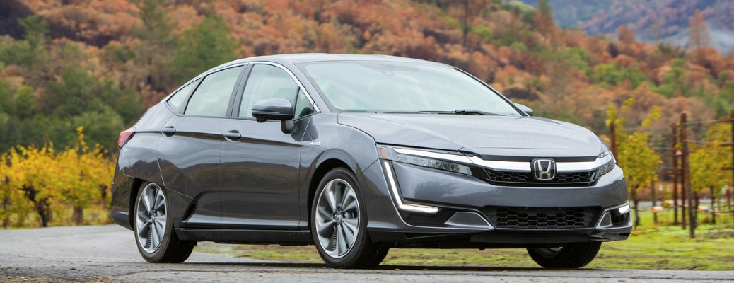 2021 Honda Clarity PHEV gray driving on road through colorful trees