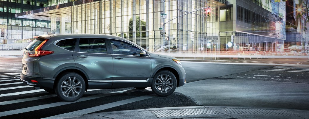 2020 Honda CR-V Touring grey driving at night to the right cityscape large glass building
