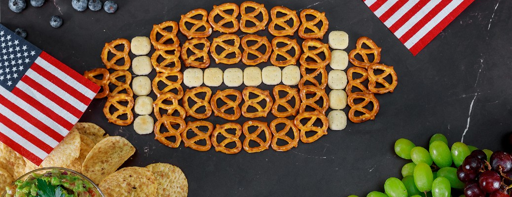 pretzels in the shape of football with chips grapes and flags