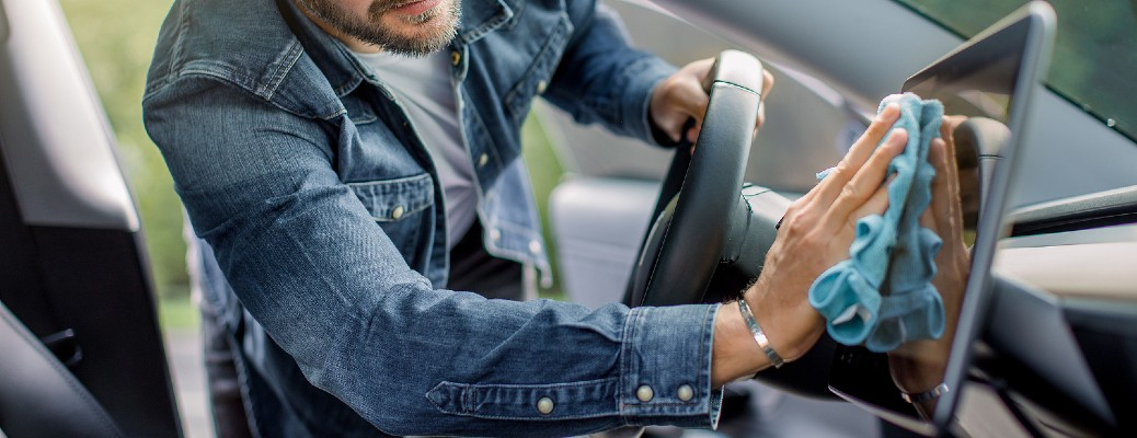 man in jean jacket cleaning car touchscreen with microfiber cloth