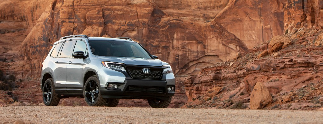 2021 Honda Passport silver parked on gravel in front of rock wall