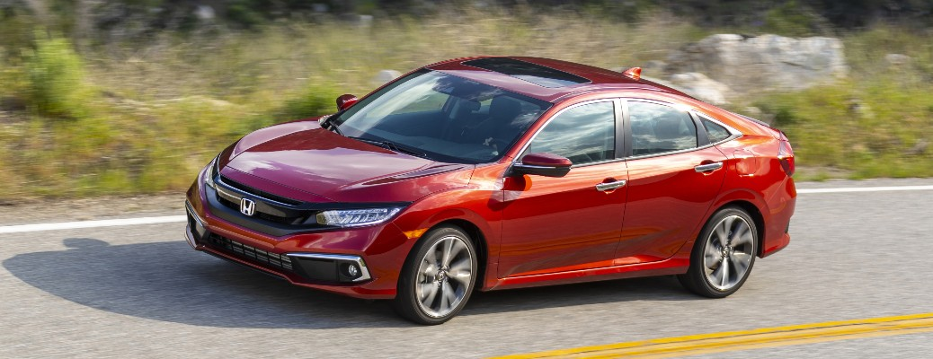 2021 Honda Civic Sedan red driving to left on road