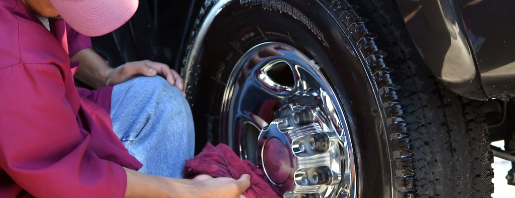 person cleaning car tires