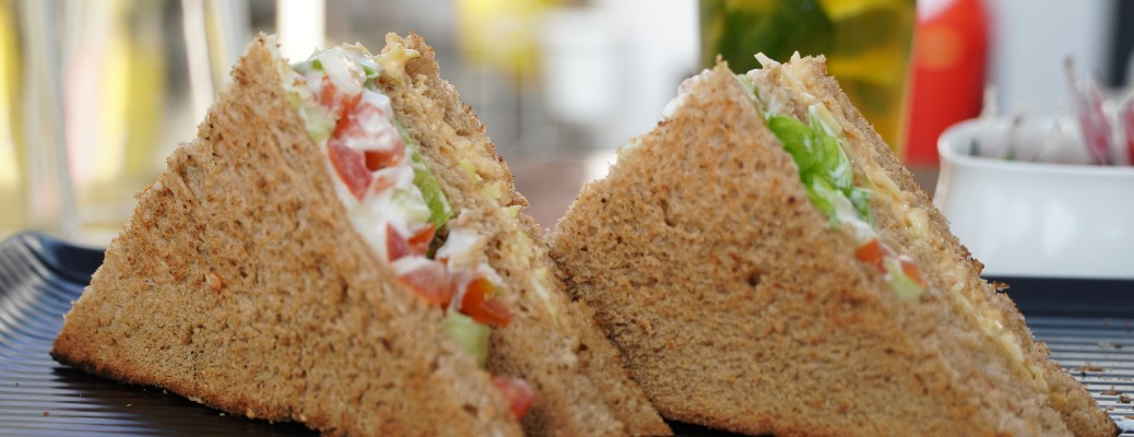two sandwiches sitting on edge on black plate with blurred background