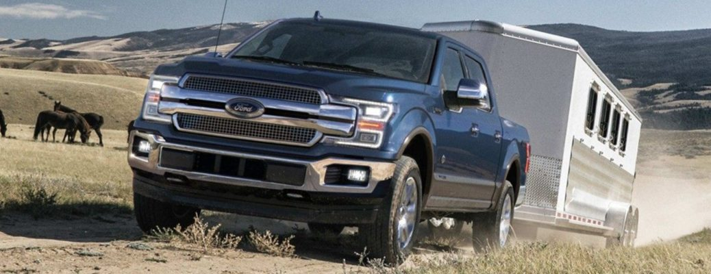 Exterior view of a blue 2019 Ford F-150 towing a camper down a dirt trail