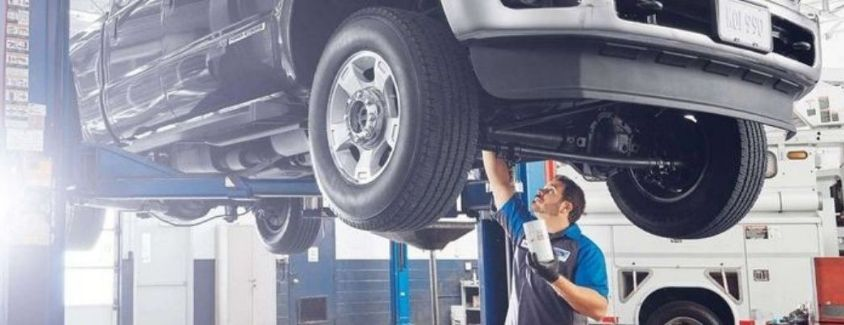 Image of a Ford Service Technician inspecting a vehicle raised up on a lift