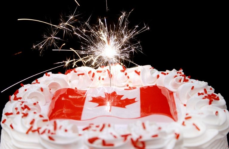 Image of a Canada Day Cake with the Canadian Flag and a sparkler instead of a candle