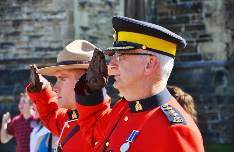 Image of two Royal Canadian Mounted Police Officers saluting during a Canada Day celebration