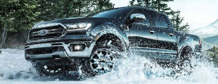 Exterior view of a black 2019 Ford Ranger driving through snow